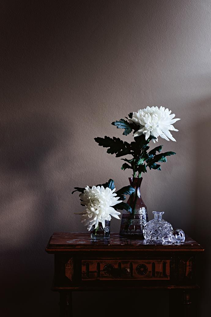 A vase of chrysanthemums sits on the French bedside table in the guest bedroom.