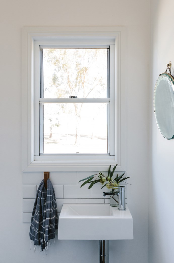 The couple sanded back old yellow paint and covered the interiors in Dulux Vivid White, to provide a crisp backdrop for the family's collected antiques — such as the powder room's vintage mirror, sourced at a humble garage sale.  | Photo: Marnie Hawson