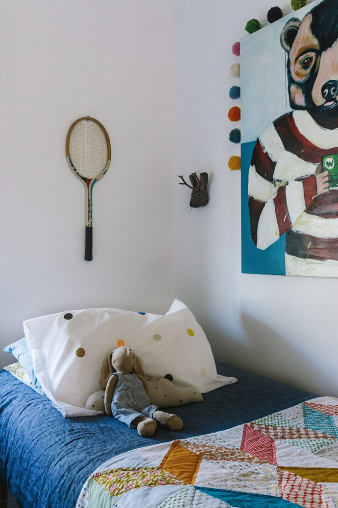 A papier-maché sculpture and vintage racquet hang above Sam's bed, which is covered with one of Susan's quilts. The painting is by Fiona Kennedy Altoft.  | Photo: Marnie Hawson