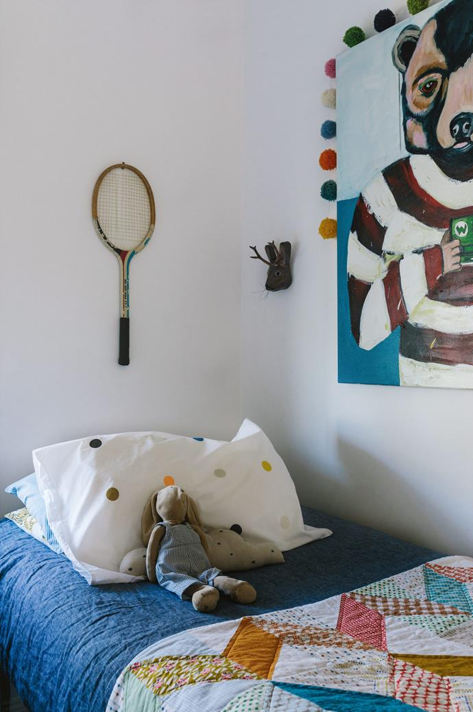 A papier-maché sculpture and vintage racquet hang above Sam's bed, which is covered with one of Susan's quilts. The painting is by Fiona Kennedy Altoft.