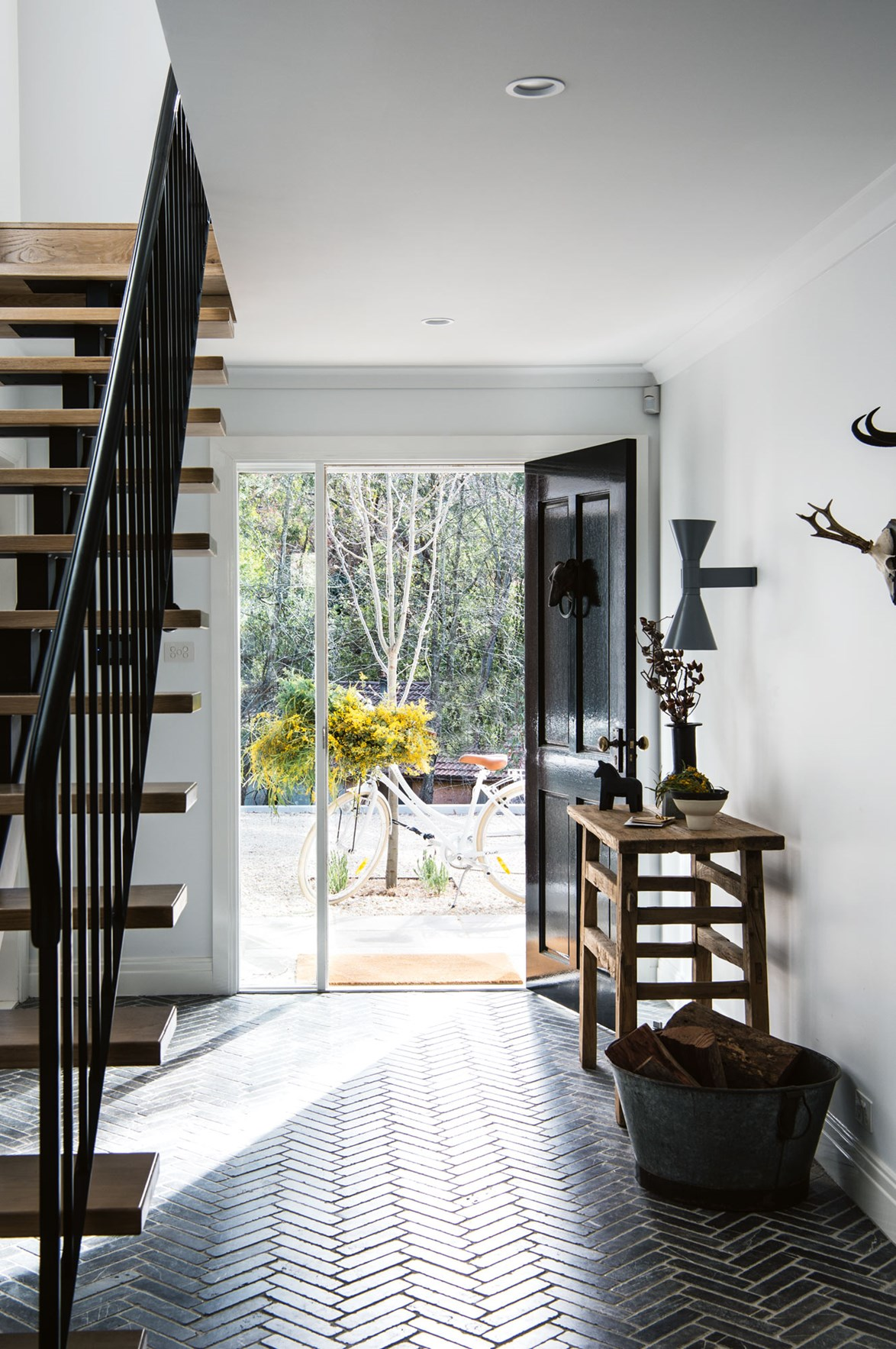"A bold black front door combined with dark herringbone floor tiles create a sense of drama in the entryway of this [modern Blue Mountains home](https://www.homestolove.com.au/white-light-filled-home-in-the-blue-mountains-nsw-13917|target=""_blank"")."