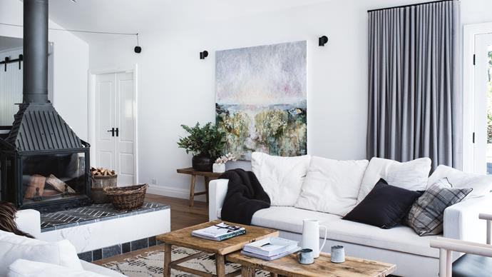 "The lounge room is a gathering space with a freestanding [fireplace as a centrepoint](https://www.homestolove.com.au/cosy-fireplaces-that-will-warm-your-heart-3475|target=""_blank""). ""Simon wanted it to be gas because he'd already gorwn up havig to chop and gather wood as a kid. But I felt that the life we wanted was one where you had to put the phone down and be in the moment, and if that means we're chopping wood, so be it!"""