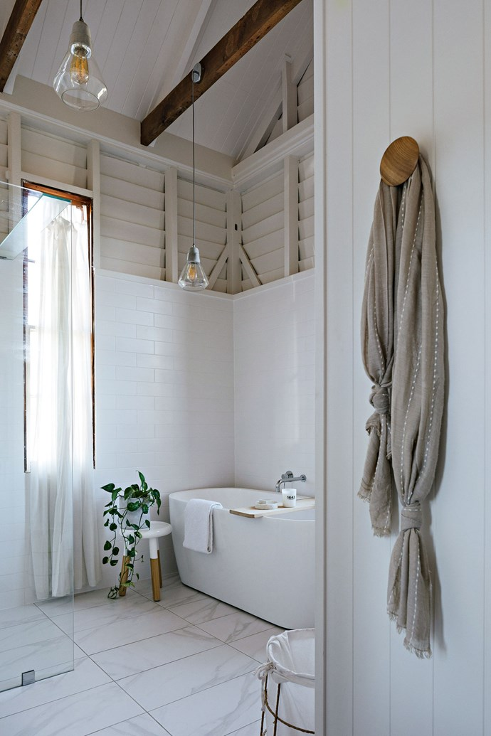 "Matte white subway tiles and a [freestanding bathtub](https://www.homestolove.com.au/freestanding-baths-4520|target=""_blank"") are a classic touch in the airy bathroom."