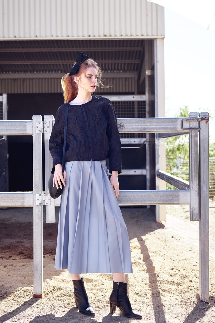 Grosgrain and straw bow headpiece, $220, from [Jane Lambert Hats](https://www.facebook.com/janelamberthats/). Textured jacket in Black, $215, and pleated skirt in Pale Blue, $135, both from [COS](www.cosstores.com/au/). Boots, model's own. | Photo: Corrie Bond