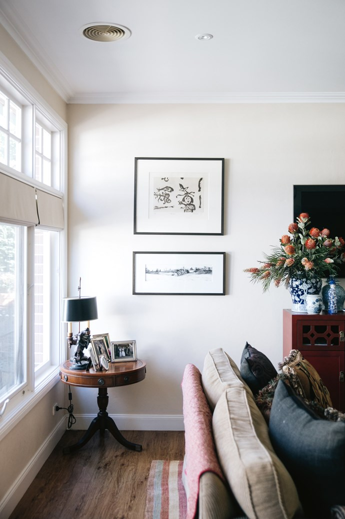 The 'Stonover Stripe' rug in the living room is Sarah's favourite. Artworks by John Olsen (top) and Peter Hickey hang above the antique side table the family brought back from the U.S.    Photo: Abbie Melle