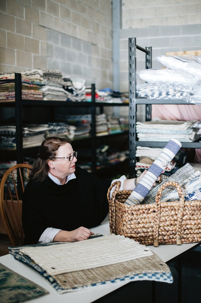 Sarah in her Mittagong warehouse, surrounded by sample swatches. Her imports of Dash & Albert offer a bold, colourful alternative to Australian-designed homewares, which are often neutral in colour.    Photo: Abbie Melle