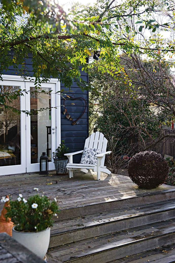 A wire sculpture bought at a country fair sits beside an Adirondack chair on the deck.