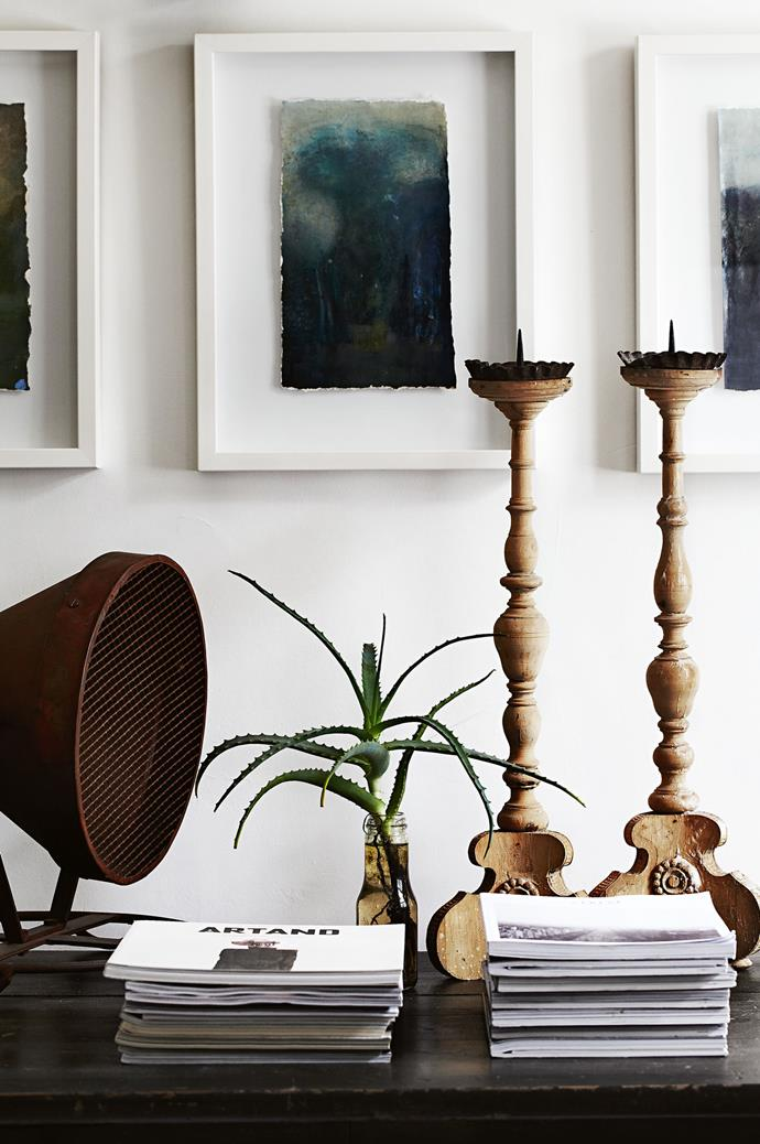 Paintings by Jenny Ryan of Melbourne's Royal Botanic Gardens above an antique fishing light and a pair of Victorian candlesticks.