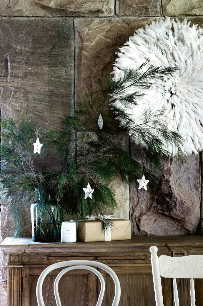 Freshly picked branches decorated with felt stars from Honeybee Homewares are arranged in a vase from The Lost and Found Department. The sideboard is from Perfect Pieces and above it hangs a feathered tribal juju hat imported from Africa.| Photo: Brigid Arnott | Styling: John Mangila