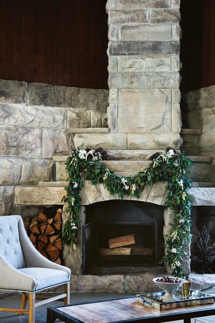 The original fireplace is decorated with a eucalyptus garland from Trille Floral. | Photo: Brigid Arnott | Styling: John Mangila
