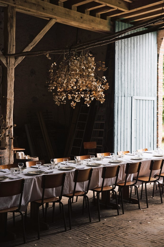 """""""My dad couldn't believe the photographs of his barn, where he parks his old tractor, transformed into a grand dining room,"""" mentions Flore. The long table was constructed with desks from the local school.  