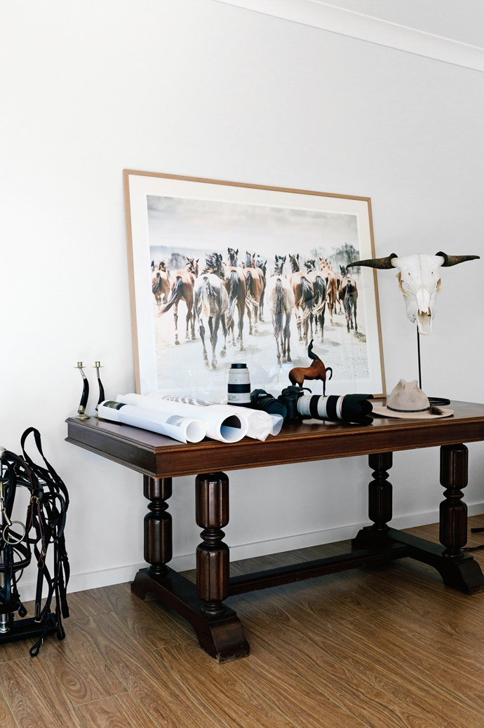 A framed coloured print entitled 'Finch Farm Horse Tails' sits on adesk in Katie's studio alongside cameras.    Photo: Marnie Hawson