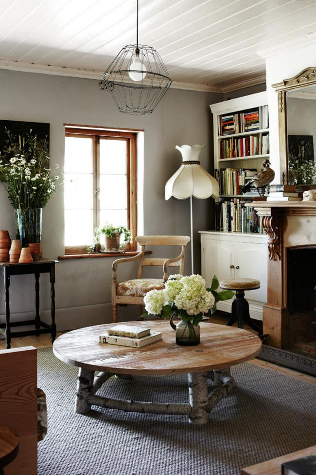Think creatively for budget-friendly decorating ideas. Here, a pile of terracotta pots enhances a floral display on a side table, while the hanging wire light cover was made by one of the owners.