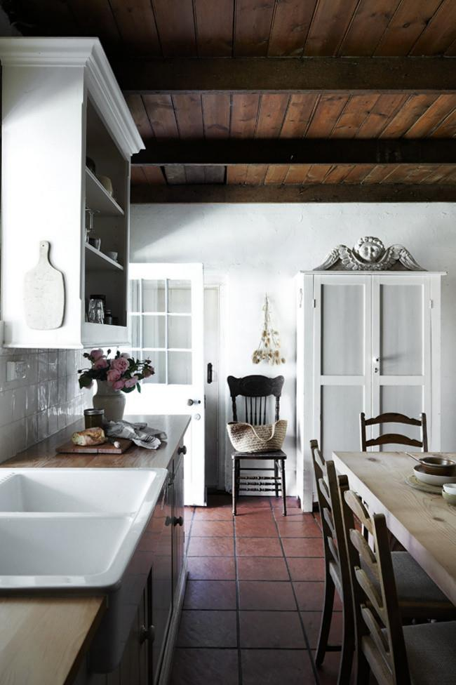 A mid-19th century shepherd's cottage has been transformed into a welcoming home. In the kitchen, the rich tones of the ceiling beams and a handmade wooden table bring warmth to balance the elegant whites used in cupboards and walls. *Photo: Sharyn Cairns*