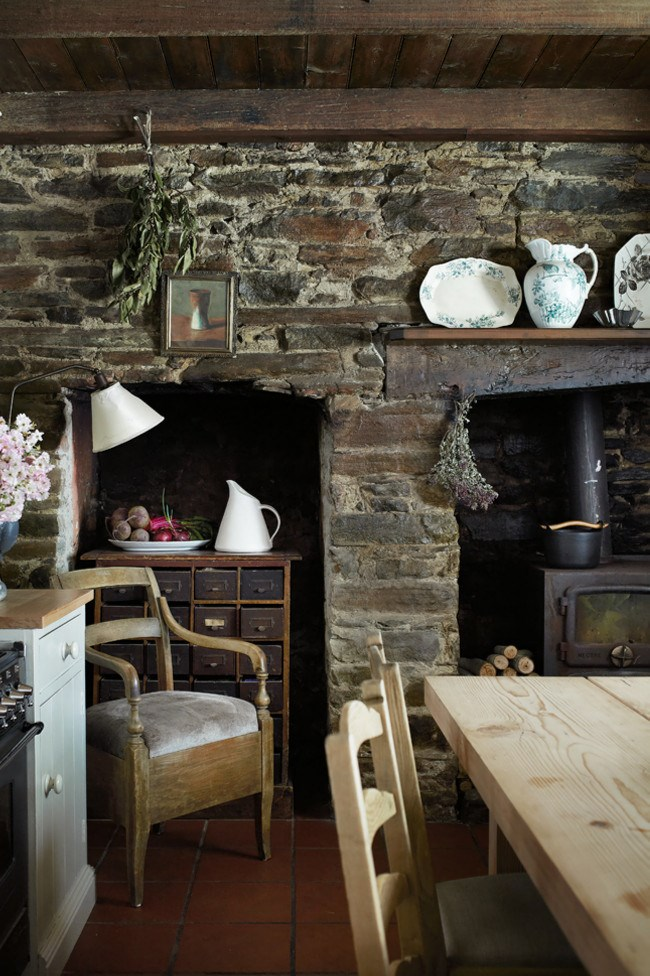 A wood-fired stove is the heart of this kitchen, where items from the owner's collection of antique crockery create a bright note against the original brick walls. *Photo: Sharyn Cairns*