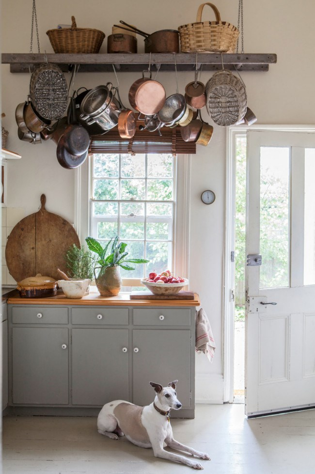 Weathered baskets and copper pots bought in markets in France hang from a suspended ladder, a clever way to add character without clutter.  *Photo: Simon Griffiths*