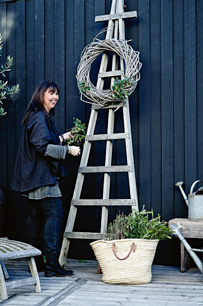 """""""Not everyone gets to be with family every year on their birthday. I love that I do. I really enjoy setting up for Christmas because it's a part of your creative side,"""" Amanda says, assembling a wreath on a ladder bought at a garage sale. Foliage sits in a basket from The Vintage Rose.  