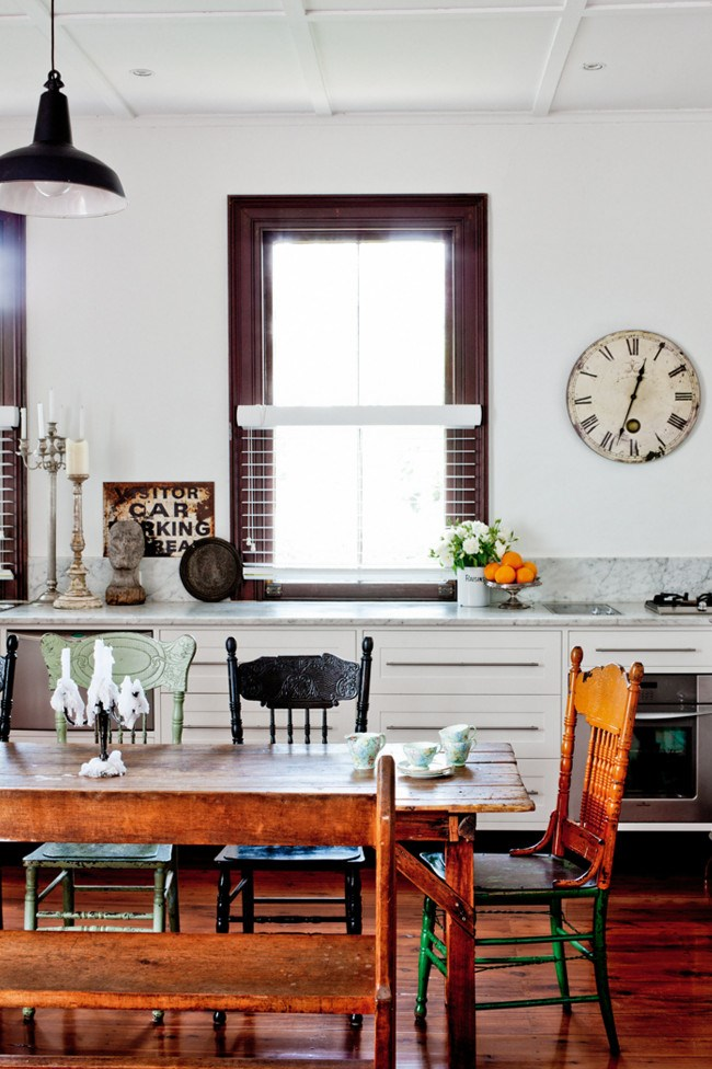 An owner's love of vintage is reflected in a room filled with preloved treasures rich with history. Play with deliberate imperfection by gathering different styles of chairs around a kitchen table and look to old-fashioned details from clocks to candlesticks. *Photo: Sam McAdam-Cooper*