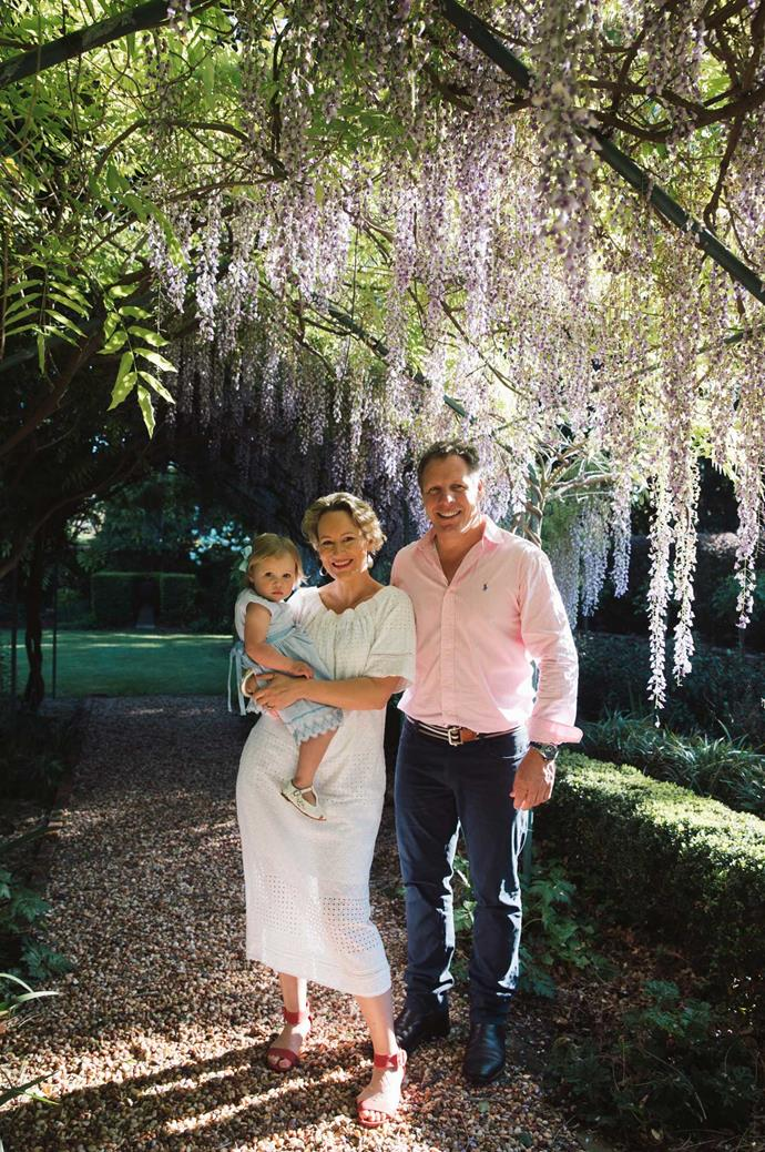 "Amelia and Todd with their two-year-old daughter, Poppy, under their garden's [climbing wisteria](https://www.homestolove.com.au/plant-guide-wisteria-9531|target=""_blank"") ceiling. ""Every season new things pop up here, and you see things you did together that actually worked,"" Amelia mentions. ""You get joy in those successes, and it's wonderful to have something in common that's not work-based."""