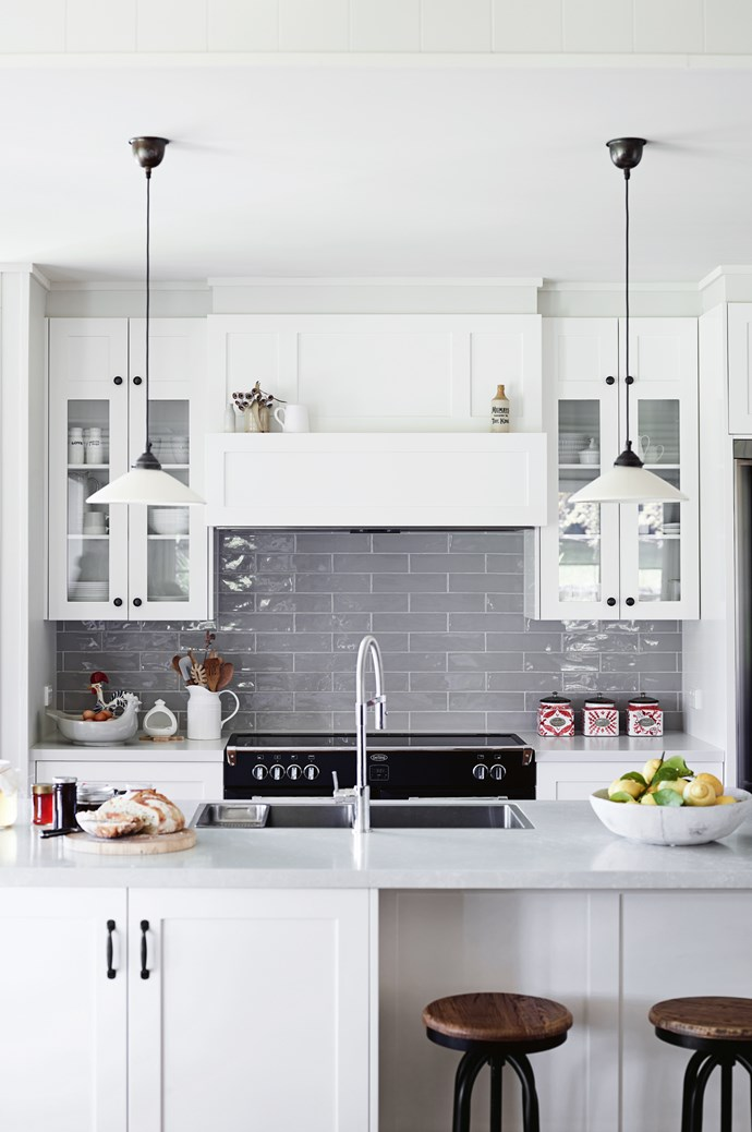 The couple regularly cook in their custom-made kitchen. Cabinetry, with a splashback of natural light grey glossy tiles, is by [Lifestiles](https://www.lifestiles.com.au/). The island benchtop is [Caesarstone](http://www.caesarstone.com.au/) 'Alpine Mist'. Emac and Lawton 'Newport' lights from [Temple and Webster](https://www.templeandwebster.com.au/) hang from the ceiling. | Photo: Mark Roper