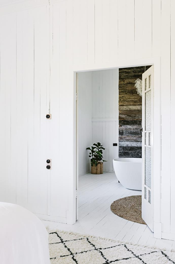"Original French doors were placed between the ensuite and bedroom. The [tub in the ensuite](https://www.homestolove.com.au/ensuite-bathroom-design-ideas-18820|target=""_blank"") is displayed in front of old cattleyard rails. ""It feels like my little sanctuary and there's no clutter,"" Maree says."