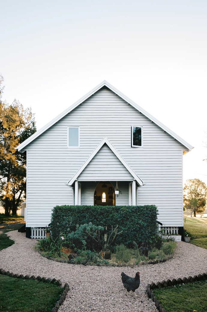 "The entrance to the church with a gravel path edged with bricks. This exterior facade was initially blue with burgundy and cream trim, so one of the couple's first tasks was to [paint it Dulux](https://www.homestolove.com.au/dulux-paint-colour-trends-2019-18959|target=""_blank"") Silkwort with Dulux Domino trim."