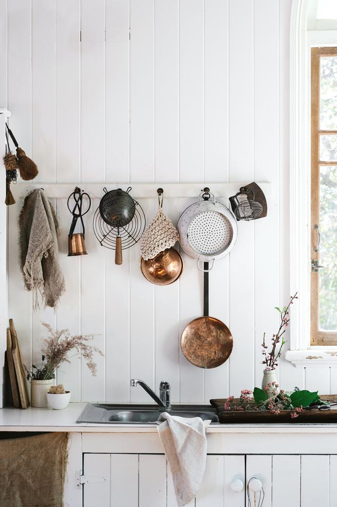 """I'm drawn to antique cooking utensils!"" proclaims Cheryl. The kitchen is a mix of cool white shades in low sheen, to accommodate sunlight entering the windows."