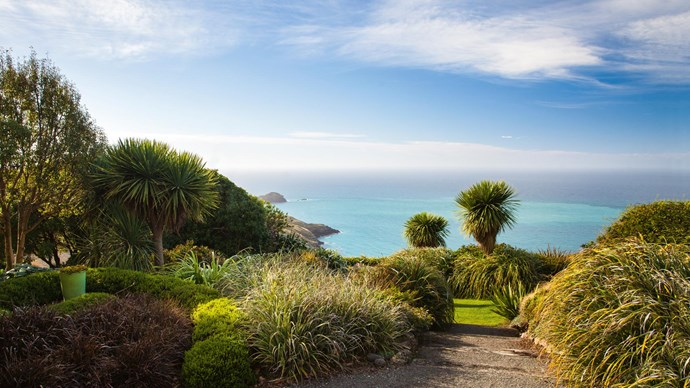 On New Zealand's Banks Peninsula, Fishermans Bay Garden seamlessly blends in with the surrounding landscape. Framed by glorious ocean views, it's tended to by Jill and Richard Simpson, a couple who are lucky enough to welcome penguins and fur seals at the bottom of their garden.  | Photo: Claire Takacs