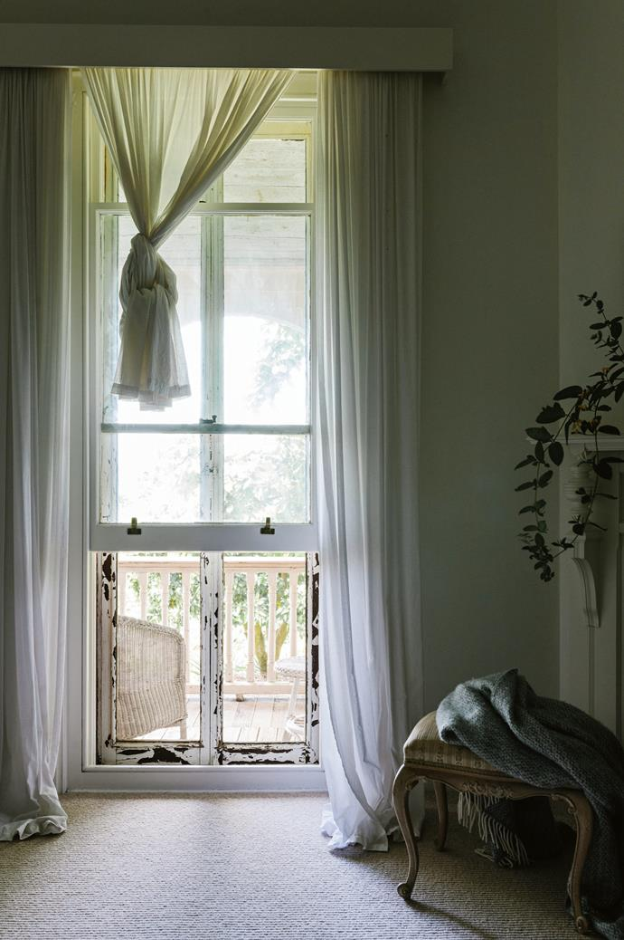 Tall windows with voile curtains to soften the light the light look out to the verandah from the bedroom.