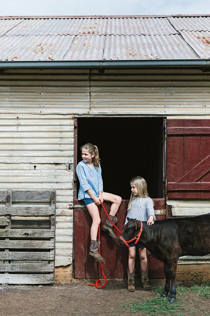 The girls relax in the cattle yard with Puddles. The children have inherited their love of the countryside.  | Photo: Marnie Hawson