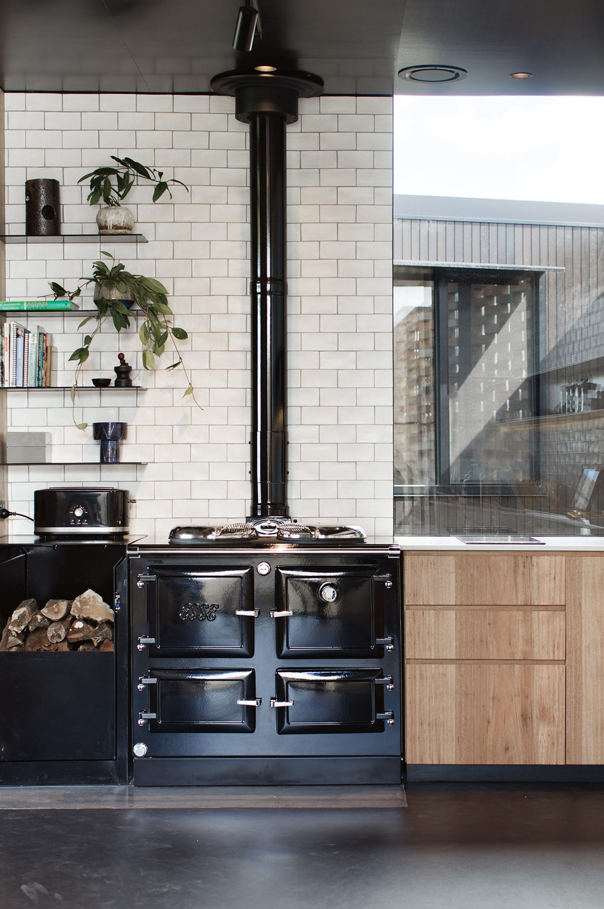 "In this kitchen of a [sustainable timber home](https://www.homestolove.com.au/sustainable-timber-home-south-gippsland-13988|target=""_blank"") overlooking South Gippsland hills, the wood stove provides heating to the whole home. ""It's a big black shinny monster called Esse, which has a wetback to provide hot water and floor heating in winter,"" says homeowner Jackie."