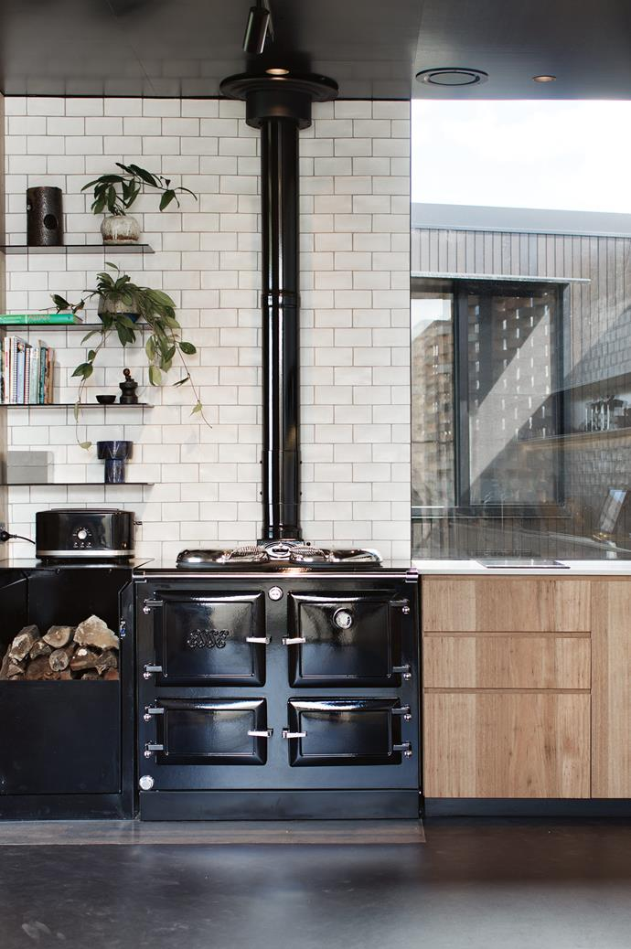 "The heart of the home, in Jackie's eyes, is the wood stove in the kitchen. ""It's a big black shinny monster called Esse, which has a wetback to provide hot water and floor heating in winter,"" mentions Jackie. The white 'Devonshire' tiles are from Bespoke Tile and Stone."