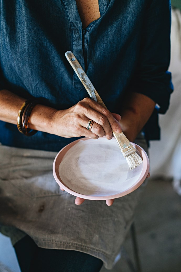 When a piece calls for a more refined touch, Anna applies a porcelain glaze. She brushes glaze onto a greenware bowl before it enters the kiln for firing.