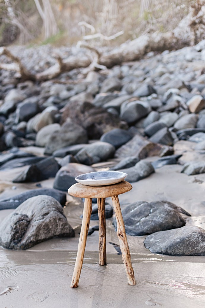 """The 'Salad for One' bowl sits atop a rustic driftwood stool. """"While my ceramics suit any aesthetic, I love seeing them in beautiful, natural settings,"""" Anna mentions."""