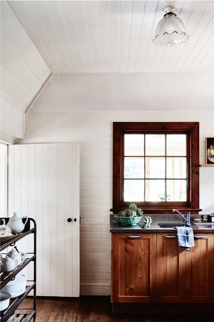 The kitchen has joinery in macrocarpa pine. On the left, a French shoe rack displays Carol's tea sets.