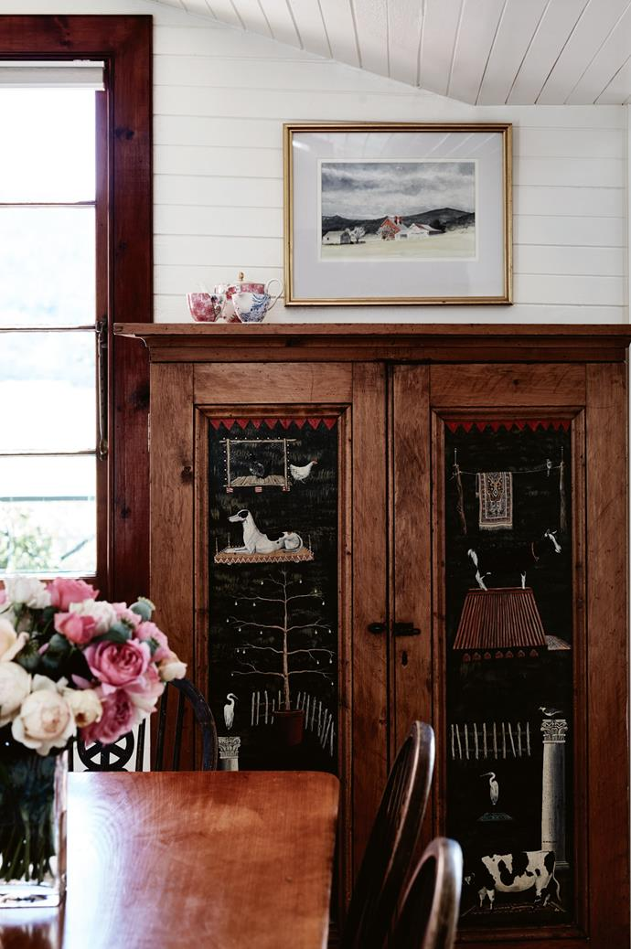 "This old King Billy pine cupboard has been decorated by Tasmanian contemporary painter, Michael McWilliams, who began his career [painting on old furniture](https://www.homestolove.com.au/upcycled-furniture-ideas-6629|target=""_blank"") from his family's antique business. The painting above the cupboard is a watercolour of Nile Farm as it was in 1962, painted by a Launceston local."