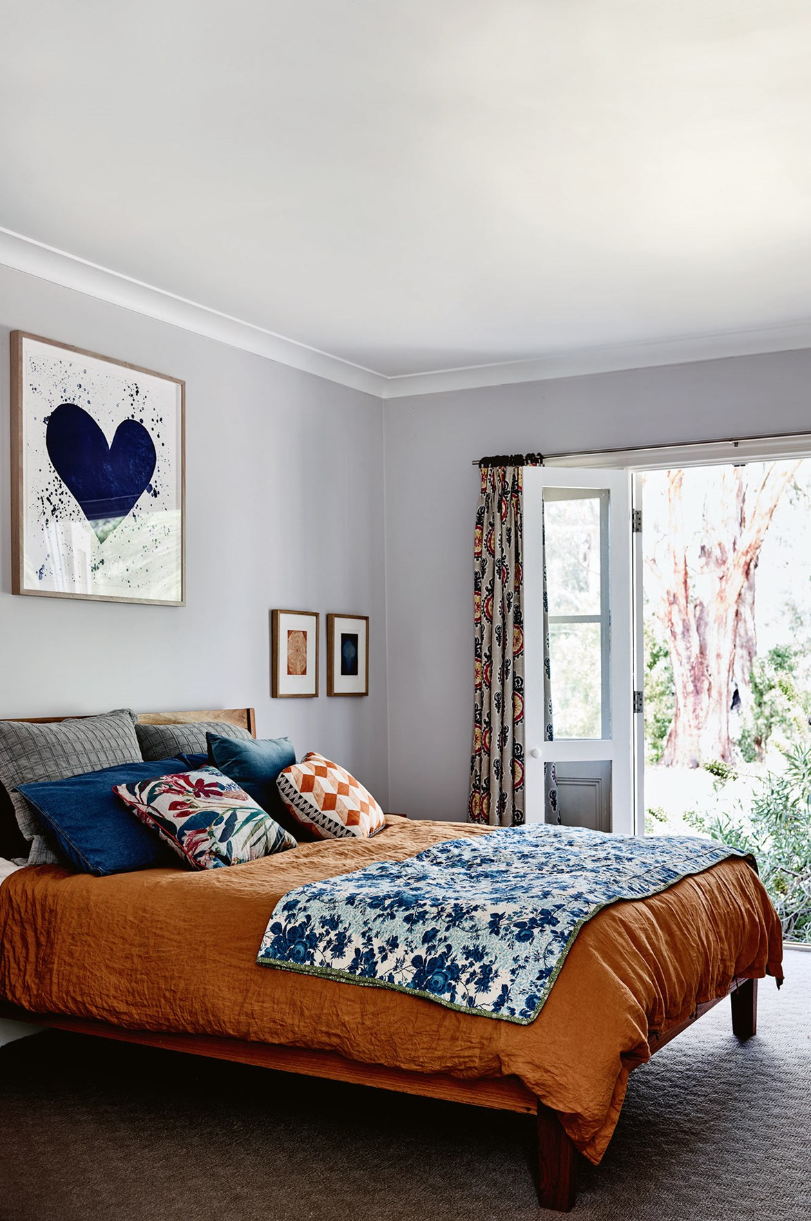 "Earthy, terracotta-coloured bedlinen and colourful artworks inject this bedroom inside an artist's [weatherboard farmhouse](https://www.homestolove.com.au/weatherboard-farmhouse-14002|target=""_blank"") in the Macedon Ranges with warmth and personality."