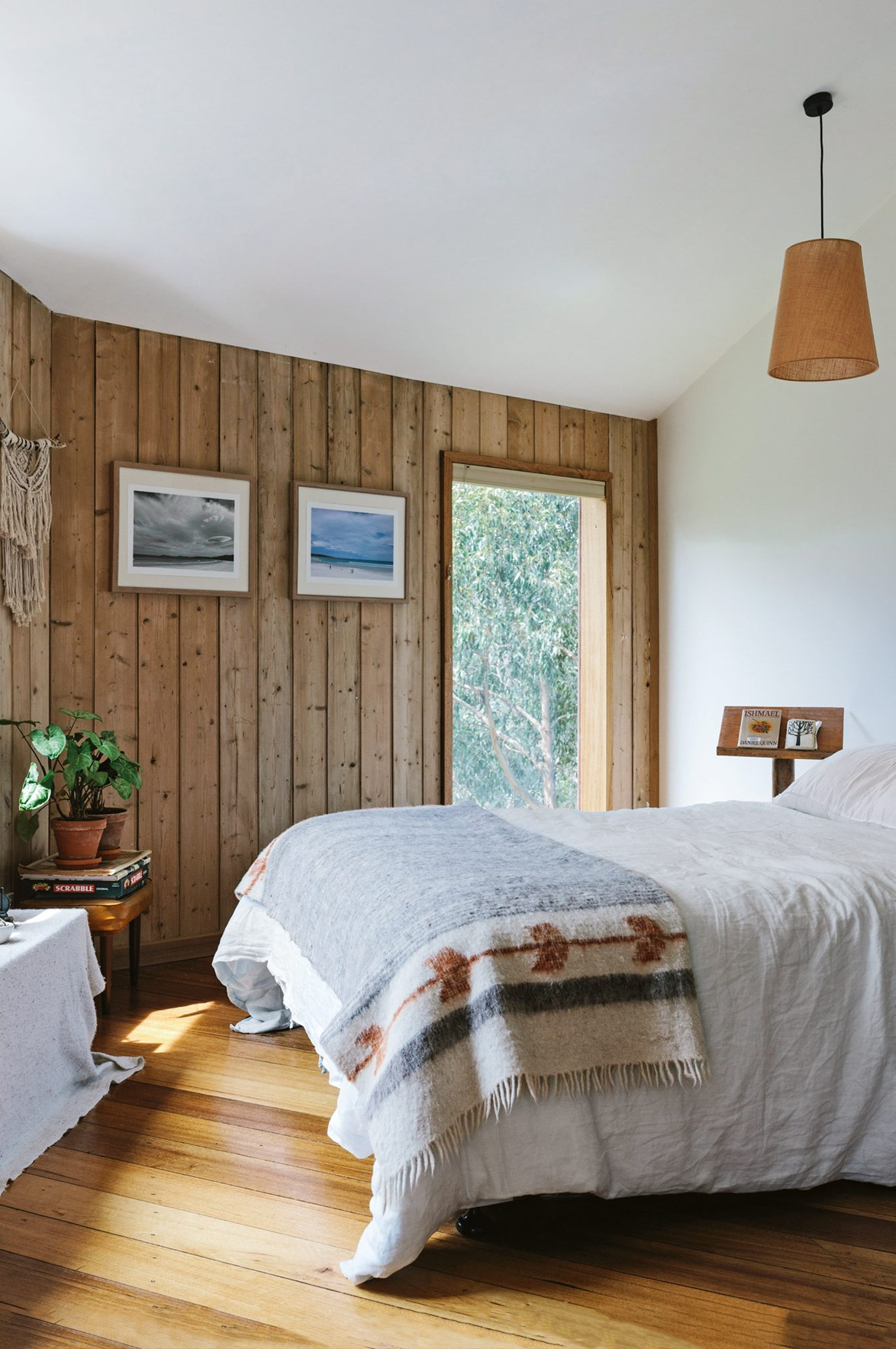 Natural light, timber wall panelling and a cosy throw brought back from Guatemala, make this simple bedroom feel warm and cosy.