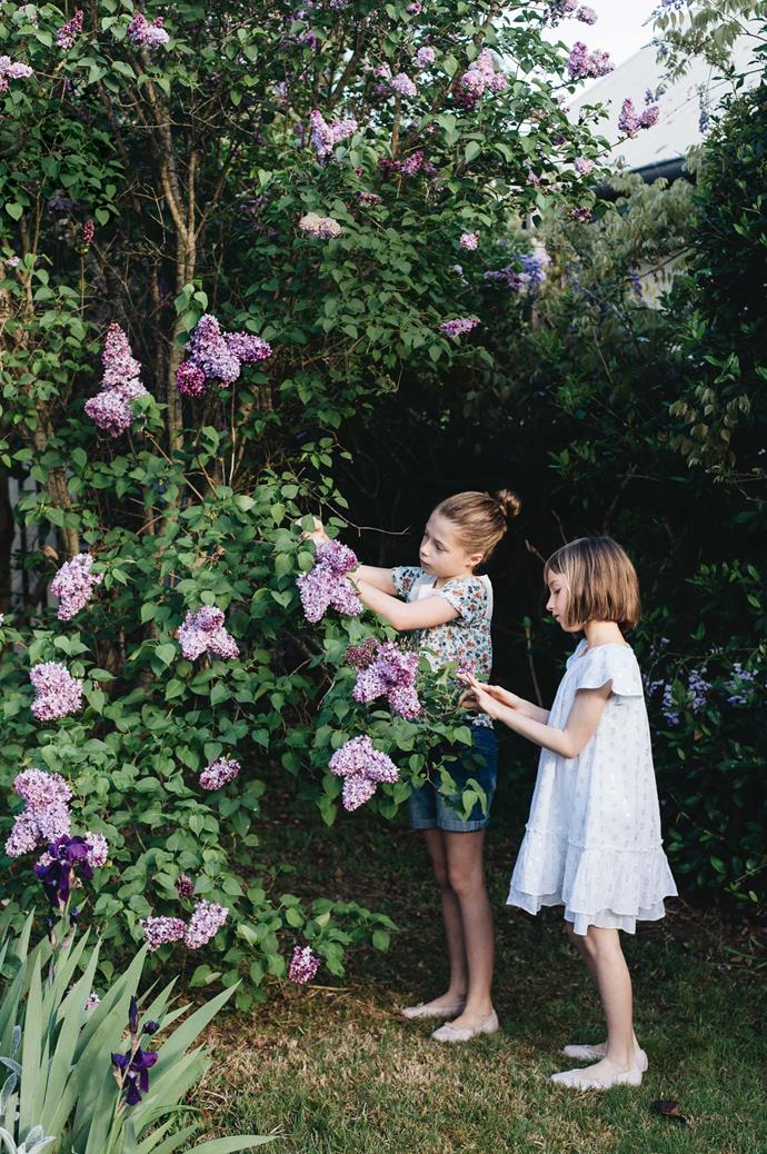 Annie and Audrey admire the lilacs in their garden.
