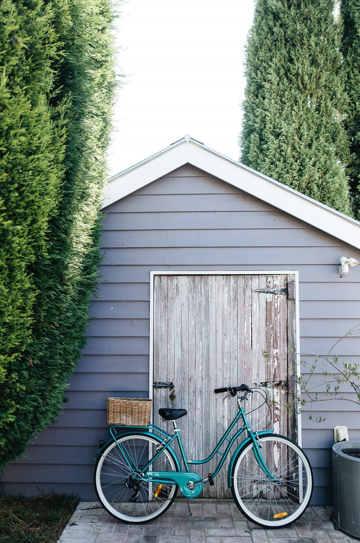 "Painting the garden shed in the same custom grey-lilac colour as the exterior of their [Southern Highlands home](https://www.homestolove.com.au/colourful-weatherboard-cottage-14022|target=""_blank"") creates a cohesive feel, making the shed feel like an extension of the house."
