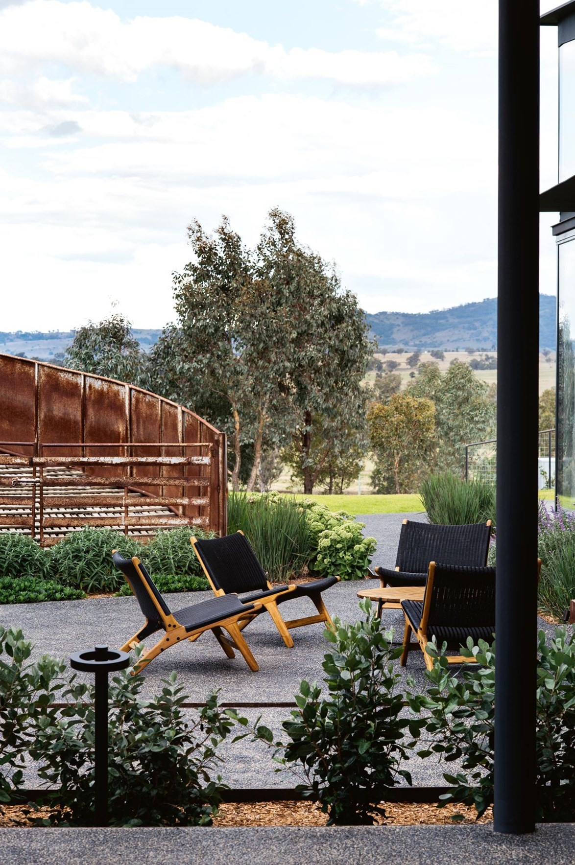 "What started as a garden project for a [historic homestead](https://www.homestolove.com.au/historic-garden-restoration-14024|target=""_blank"") quickly evolved to take on the surrounding – and expansive outdoor space. This casual seating area is the perfect spot to sit an admire the landscaped gardens and views of the surrounding paddocks and mountains."