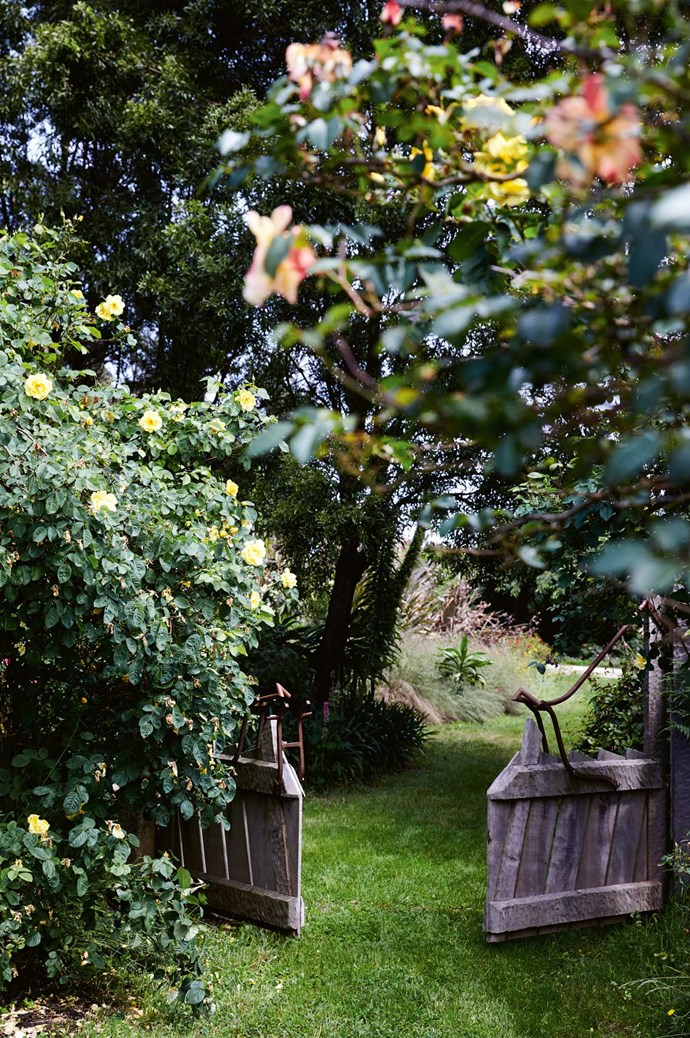 """[Garden gates](https://www.homestolove.com.au/beautiful-garden-gates-13737 target=""""_blank"""") made by local craftsman and builder Paul Noordanus, who used salvaged wood and other timber to create structures throughout the garden."""