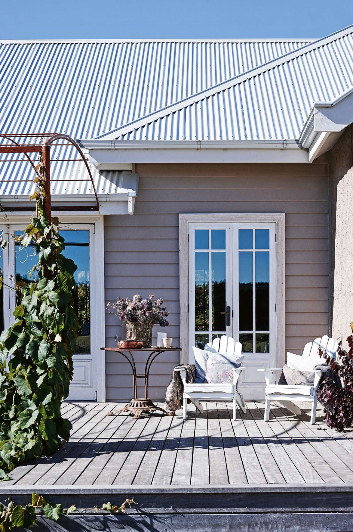 "The rear deck of this [farmhouse in Victoria's Macedon Ranges](https://www.homestolove.com.au/share-house-a-family-farmhouse-in-the-macedon-ranges-14014|target=""_blank"") overlooks the garden and paddocks. The homeowner made the arbour for the crimson glory vine. ""On summer evenings, I love curling up on my favourite cane chair overlooking the paddocks and the colours of the garden harmonising with the setting sky,"" Kate muses."