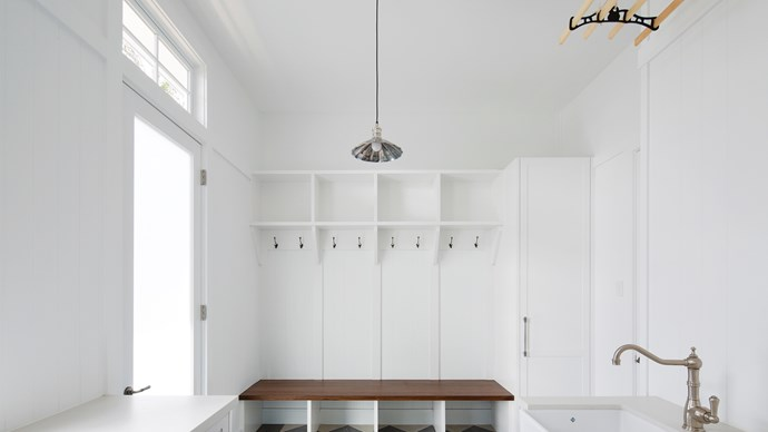 4. Make your storage space versatile by opting for fresh and bright whites, illuminated by natural light. Inspired by Hamptons style, this laundry and mudroom is a space entirely reserved for kids to kick off their shoes and store their school bags, coats and hats.  | Photo: Simon Whitbread