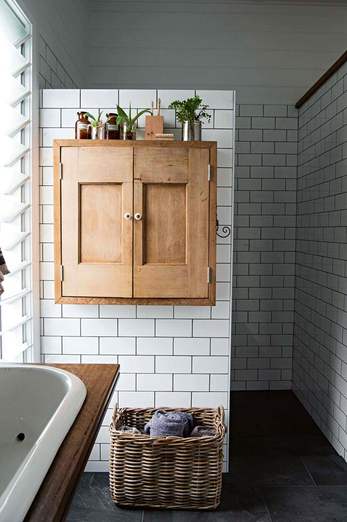 """This ensuite has character in spades, with the addition of a wall-mounted cupboard made from old doors and a custom vanity bench surrounding a vintage enamel baby bath from [The Society Inc.](https://thesocietyinc.com.au/