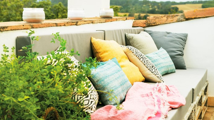 Compose a bold colour palette with your cushions, to combat weary winter blues. As night falls, light up a few scented candles to relax on your balcony. Image courtesy of [El Mueble](http://www.elmueble.com/)