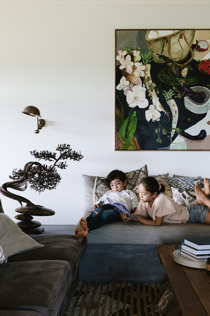 Arthur and Soraya relax on the daybed. Above them hangs 'Daikon Still Life', a Laura Jones painting. Palisa found the intricate metal bonsai by Wanupong Khahokaew at an art far in Bangkok. The Lincolns swing arm wall sconce is from [Emac and Lawton](http://www.emac-lawton.com.au/). | Photo: Marnie Hawson