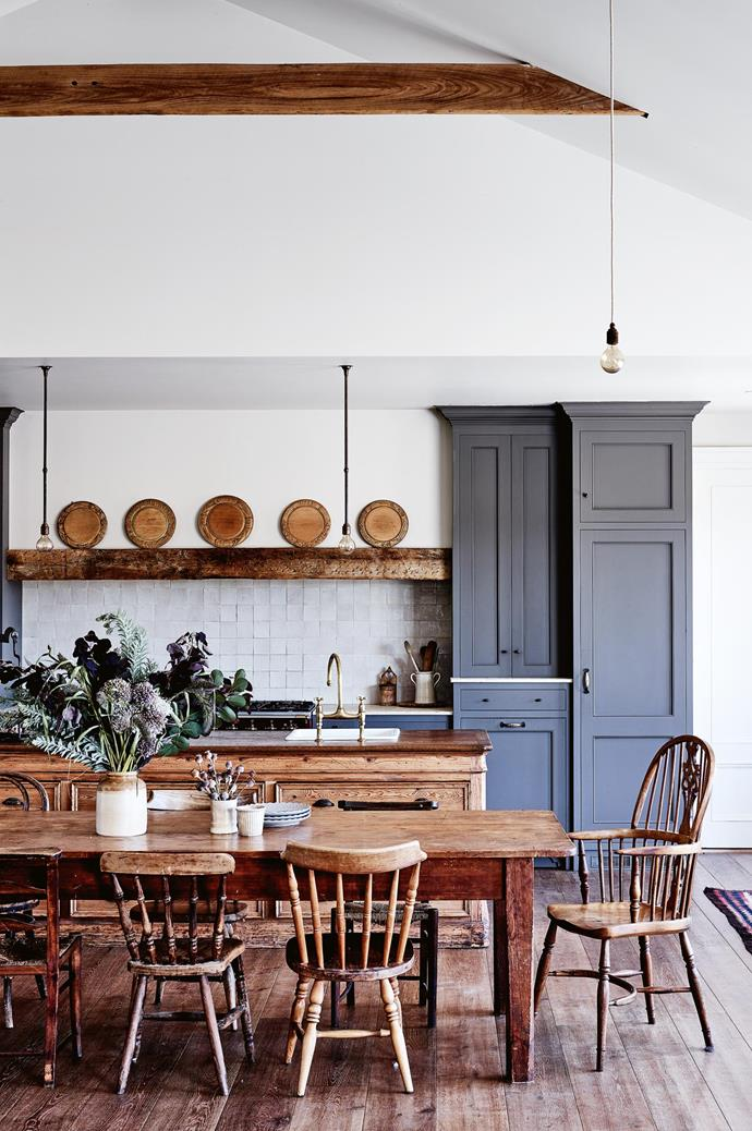 "This kitchen, belonging to a [family farmhouse in the Macedon Ranges](https://www.homestolove.com.au/share-house-a-family-farmhouse-in-the-macedon-ranges-14014|target=""_blank""), was actually designed around the antique wooden beam, which displays a collection of bread boards. The dining table was gifted to the family from a friend, and links the kitchen to an open-plan living area."