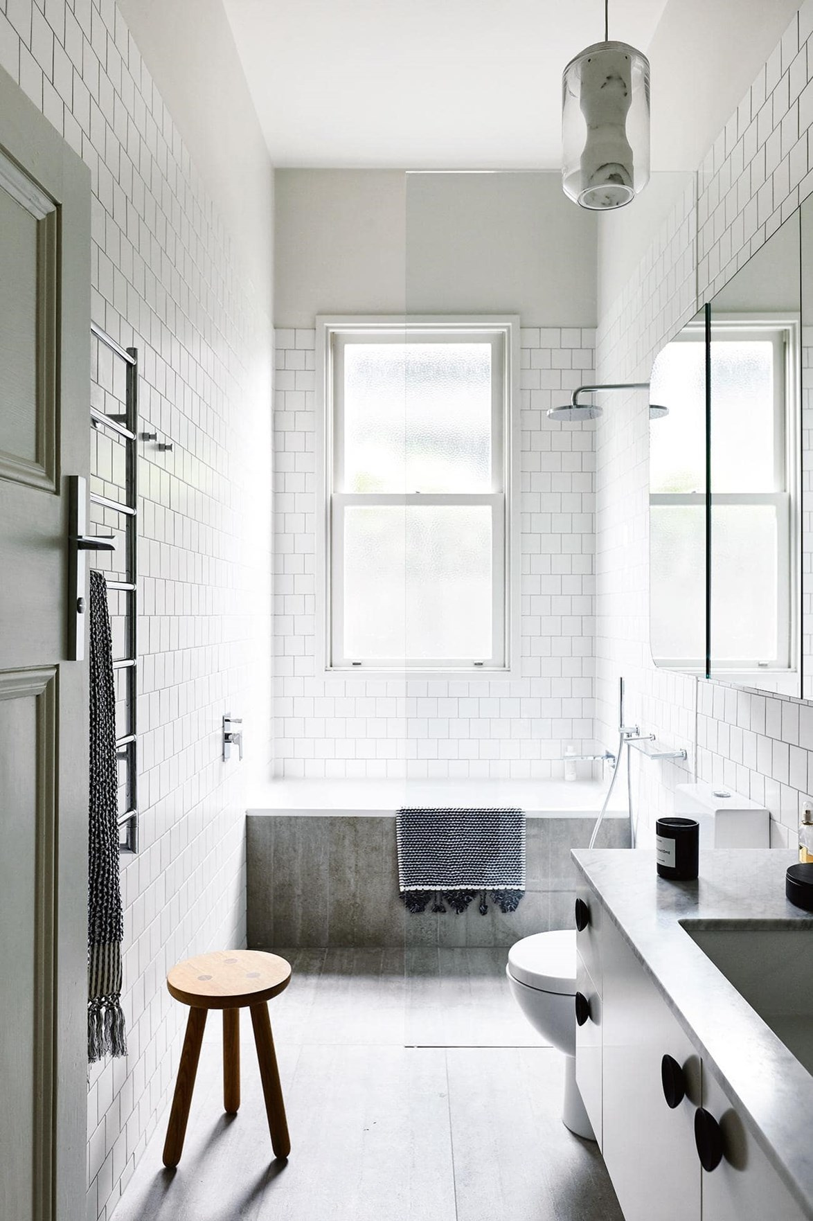 Tonal grey flooring helps to ground this narrow bathroom with high-ceilings. Classic subway tiles are a nod to the home's Edwardian heritage. *Photo: Derek Swalwell / Styling: Bek Sheppard*