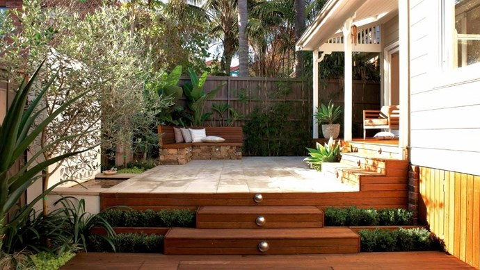 """The upper level of this outdoor area is paved with Himalayan honed sandstone which plays up all the available light while the built-in bench is mostly constructed from hardwood. [Water-wise plants](https://www.homestolove.com.au/a-guide-to-water-wise-gardening-3691 target=""""_blank"""") such as succulents and bamboo were chosen for their hardy, low-maintenance qualities. *Photo:* Michael Wee   *Styling:* Phoebe McEvoy"""